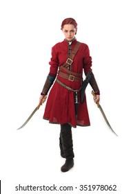 中世の赤いチュニックと革の鎧を身に着けた、若くて魅力的な赤い髪の女性の戦士。剣を武器として持ち、カメラに向かって歩きます。白い背景で隔離されました。