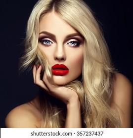 明るい化粧と黒い背景に健康的な巻き毛の彼女の顔に触れる赤い唇の美しい金髪の女性モデルの女性の官能的な魅力の肖像画