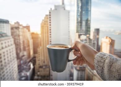 朝にニューヨーク市マンハッタンのダウンタウンを望む豪華なペントハウスアパートメントでコーヒーカップを保持している男