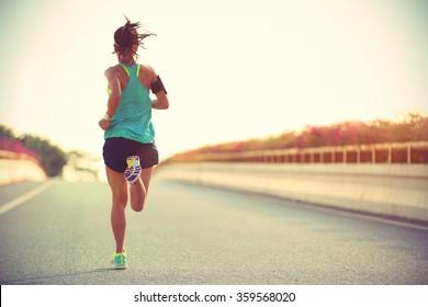 シティブリッジロードを走っている若い女性ランナー