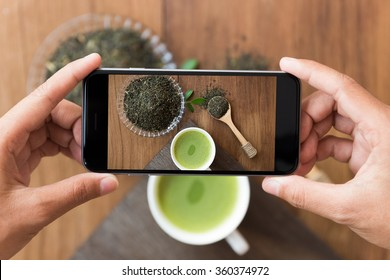 closeup hand holding phone shooting drink photograph