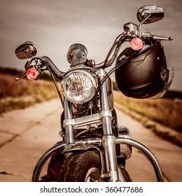 Motocicleta en carretera con casco en el manillar.