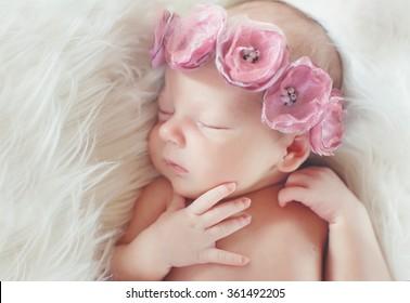 クローズアップの美しい眠っている女の赤ちゃん。生まれたばかりの赤ちゃんの女の子、毛布で眠っています。大きな布製のバラのヘッドバンドを身に着けている美しい生後7日の生まれたばかりの赤ちゃんの女の子の肖像画。クローズアップ写真