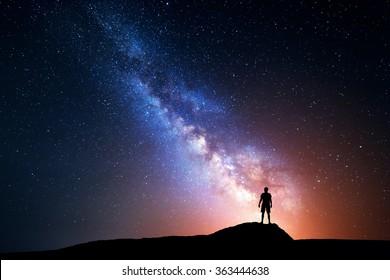 Milchstraße. Nachthimmel mit Sternen und Silhouette eines stehenden glücklichen Mannes mit gelbem Licht. Raumhintergrund