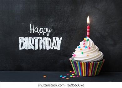 Cupcake de cumpleaños delante de una pizarra