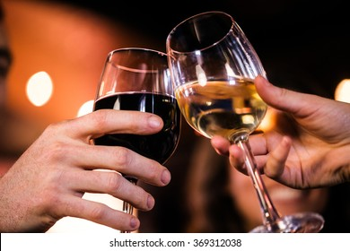 Close up of friends toasting with red and white wine