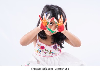 Cute little Indian girl showing her colourful hands/palm printing or playing holi festival with colours, isolated over white background