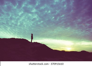 Back light silhouette of a man standing on a hill, overlooking, filtered vintage - future, power, achievement concept