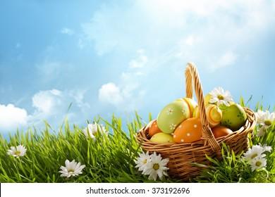 晴れた日に緑の芝生にイースターエッグのバスケット。
