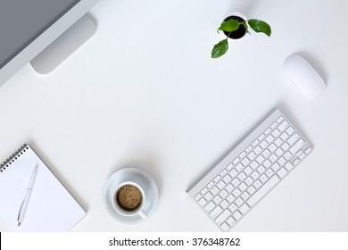 Vista superior del lugar de trabajo de tecnología moderna en el escritorio de oficina blanco con una gran computadora de escritorio Taza de café Teclado y mouse Flor verde Bloc de notas y bolígrafo