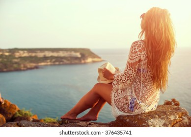 Young woman in hat and cute summer dress standing on the stone, looking at sunset over the sea