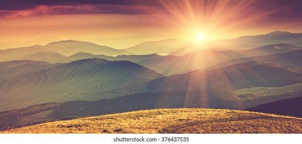 Panorama-Berglandschaft im Frühjahr mit Sonnenlicht. Gefiltertes Bild: Kreuzverarbeiteter Vintage-Effekt.