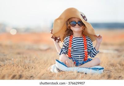 Niña bonita en un vestido rayado y un sombrero que se relaja en la playa cerca del mar, verano, vacaciones, concepto del viaje. sonriente niña linda en vacaciones en la playa. Niña con sombrero y gafas de sol en la playa
