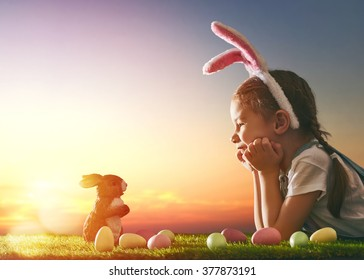 Симпатична мала девојка која носи буши уши на Велигденскиот ден. Девојчето лови за велигденски јајца на тревникот. Девојка со велигденски јајца и зајаче во зраците на зајдисонцето.