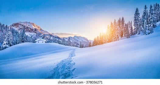 伝統的な山小屋と美しい冬のワンダーランド山の風景のパノラマビュー、夕暮れ時の黄金の夜の光の中でアルプスの背景