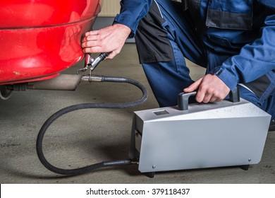 Ein Diagnosesensor wird von einem Mechaniker auf den Auspuff eines Autos angewendet, um die Zusammensetzung und die Substanzen in den Abgasen zu messen