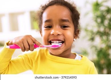 Niña africana hermosa que se cepilla los dientes, concepto sano