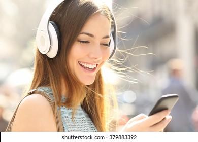 Porträt eines glücklichen Mädchens, das Musik online mit drahtlosen Kopfhörern von einem Smartphone in der Straße an einem sonnigen Sommertag hört