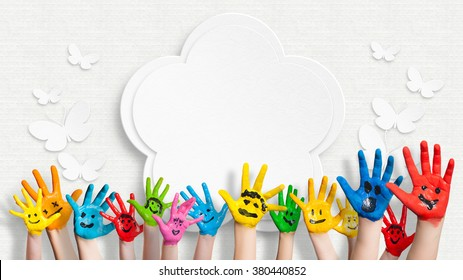 bunt bemalte Hände vor einer verzierten Wand mit einer Blume und Schmetterlingen