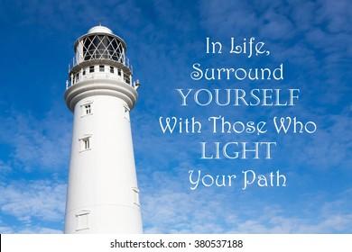 Leuchtturm mit einem inspirierenden Motivationszitat von In Life Surround Yourself mit denen, die Ihren Weg vor einem teilweise bewölkten Himmel Hintergrund beleuchten