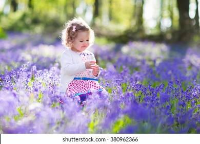 日当たりの良い咲く庭で遊ぶ少女。復活祭の卵の赤ちゃんは青い鐘花の牧草地で狩り。ブルーベルの花を摘む幼児子供。子供たちは屋外で遊ぶ。子供連れの家族のための春の楽しみ。
