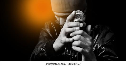 ダイナミックマイクを保持しているアジアのハンサムな歌手。黒で隔離