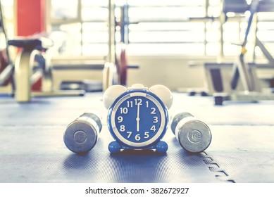 目覚まし時計を行使し、ジムの背景をダンベルする時間。共有時間運動健康概念