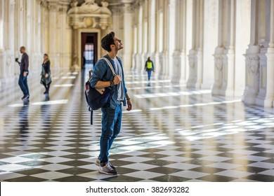 Hübscher Mann, der einen Führer innerhalb eines Museums hält