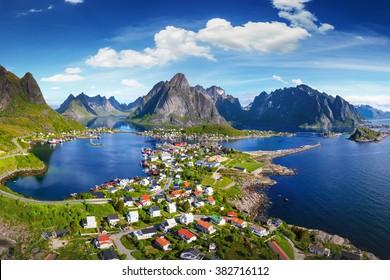 Reine, Lofoten, Norwegen. Das Dorf Reine unter einem sonnigen, blauen Himmel mit den typischen Rorbu-Häusern. Ausblick von Oben