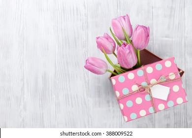 Flores rosadas frescas del tulipán en caja de regalo en la tabla de madera. Vista superior con espacio de copia