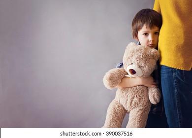 Trauriges kleines Kind, Junge, seine Mutter zu Hause umarmend, isoliertes Bild, Kopierraum. Familienkonzept