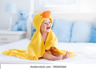 お風呂やシャワーの後に両親のベッドに座っている黄色のフード付きアヒルのタオルを身に着けている幸せな笑う赤ちゃん。寝室で乾いた子供をきれいにします。小さな子供たちの入浴と洗濯。子供の衛生。乳幼児用テキスタイル。