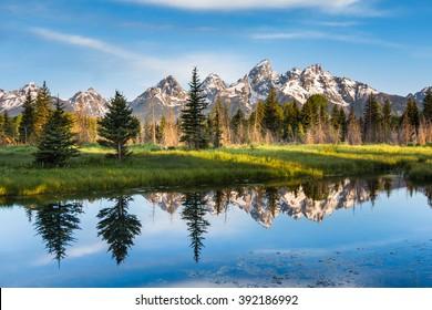 Una cordillera con su reflejo, el Parque Nacional Grand Teton, Estados Unidos. El paisaje es único y forma parte de las Montañas Rocosas. El Parque Nacional Grand Teton también es popular entre los fotógrafos de paisajes y naturaleza.