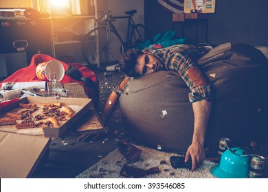 Er ist weg. Junger gutaussehender Mann ohnmächtig auf Sitzsack mit Joystick in der Hand in unordentlichem Raum nach der Party