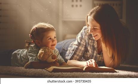 familia feliz madre e hija leen un libro en la noche en casa