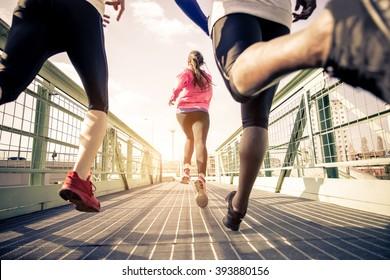 屋外で疾走する3人のランナー-都市部でトレーニングするスポーツの人々、健康的なライフスタイルとスポーツの概念