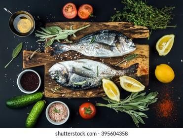 Frischer ungekochter Dorado oder Seebrassenfisch mit Zitrone, Kräutern, Öl, Gemüse und Gewürzen auf rustikalem Holzbrett über schwarzem Hintergrund, Draufsicht