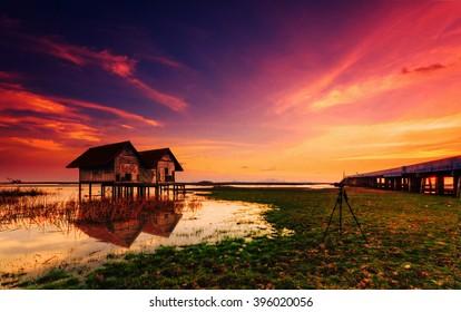 写真家がぼやけた背景のあるタイの写真に惹かれる夕方の明かりのある廃屋。