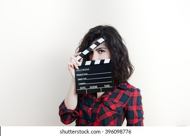 Young woman in red shirt showing movie clapper board on white background