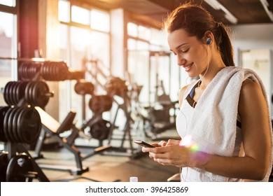 フィットネスジムでスマートフォンを使用してアクティブな女の子。