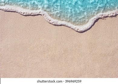 Weiche Welle des blauen Ozeans am Sandstrand. Hintergrund.