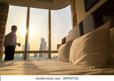 Bed maid-up with white pillows and bed sheets in cozy room. Young businessman with cup of coffee standing at window looking at city scenery on the background. Focus on cushion. Motivation concept