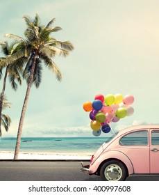 Uitstekende kaart van auto met kleurrijke ballon op concept van de strand het blauwe hemel liefde in de zomer en huwelijkswittebroodsweken