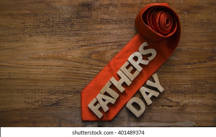 Happy Father's Day inscription with letters on wooden table background. Orange tie
