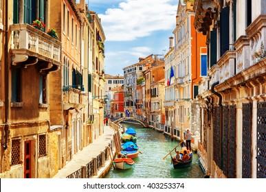 Blick auf den Rio Marin-Kanal mit Booten und Gondeln von der Ponte de la Bergami in Venedig, Italien. Venedig ist ein beliebtes Touristenziel in Europa.