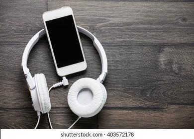 Weiße Kopfhörer und Smartphone auf Holztisch