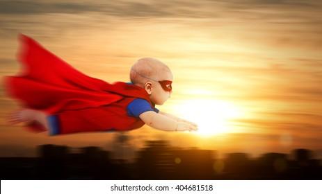 kleiner Baby-Superheld des Kleinkindes mit einem roten Umhang, der durch Sonnenuntergangshimmel über der Stadt fliegt