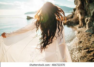chica corriendo soñadora con viento en el pelo y sunflare en la playa al atardecer. desenfocar