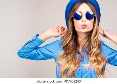 Coole Hipster-Studentin, die eine Brille trägt. Kaukasischer weiblicher Universitätsstudent, der Kamera glücklich lächelnd betrachtet.