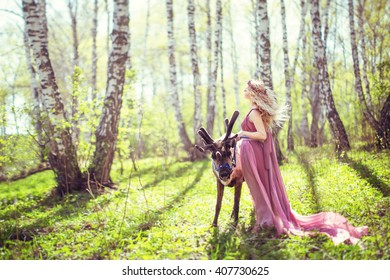 Girl in fairy dress and reindeer in the forest